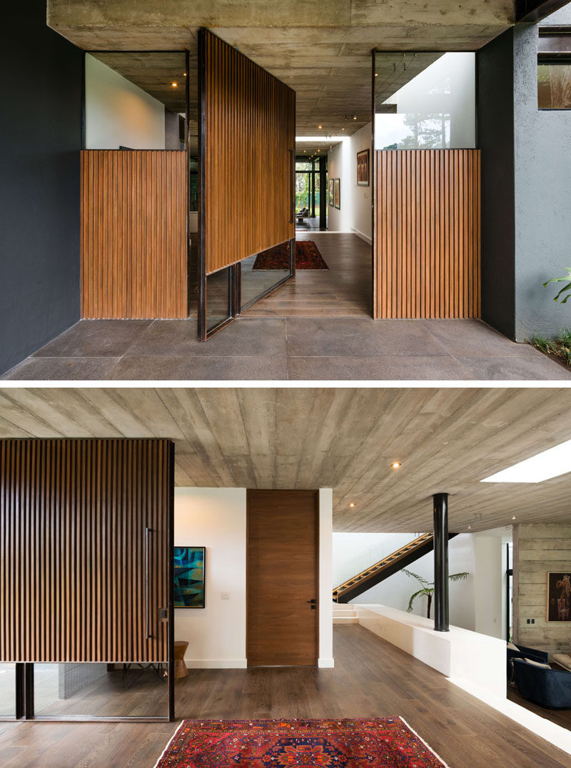 A large pivoting wood and glass front door welcomes people to this modern house. #FrontDoor #ModernFrontDoor #PivotingWoodFrontDoor