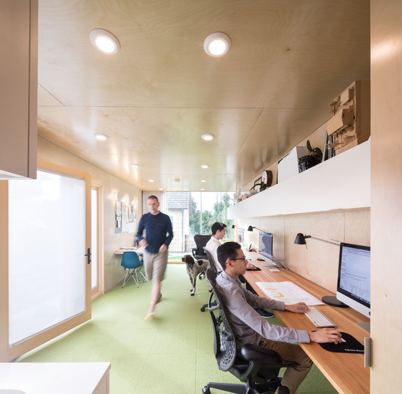 The interior of of this modern shipping container office office is lined in birch plywood to create a sense of warmth, and the Douglas Fir desk, which runs along one wall, spans 19 feet, providing a flexible working space. #ShippingContainerOffice #HomeOffice #InteriorDesign #Workplace