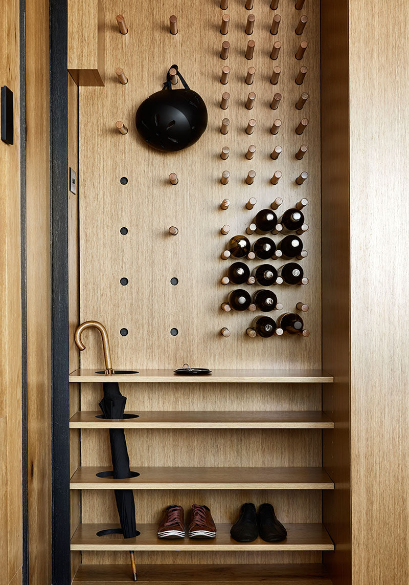Upon entering this modern and small apartment, there's a custom designed wall unit that features a flexible pegboard wall, creating a place to hang jackets, keep umbrellas and store shoes. The other half of the pegboard wall has fixed dowels to create wine storage. #Entryway #Storage #ShoeStorage #UmbrellaStand #WineStorage
