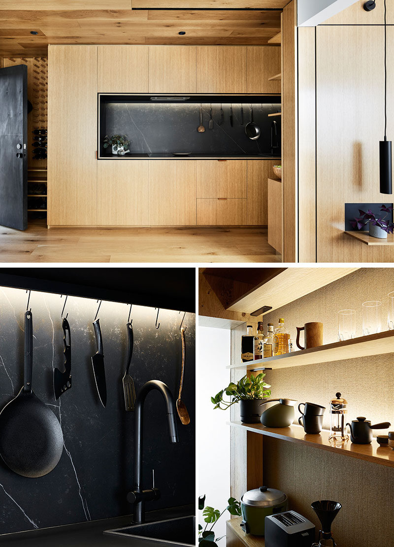 This modern and small kitchen, surrounded by wood, is 13 feet long, with the fridge and a washing machine hidden within the kitchen cupboards. Black has been used to contrast the wood, from the matte black countertop, to black sink and taps, and kitchen utensils. #WoodKitchen #WoodAndBlackKitchen #ModernKitchen #KitchenDesign