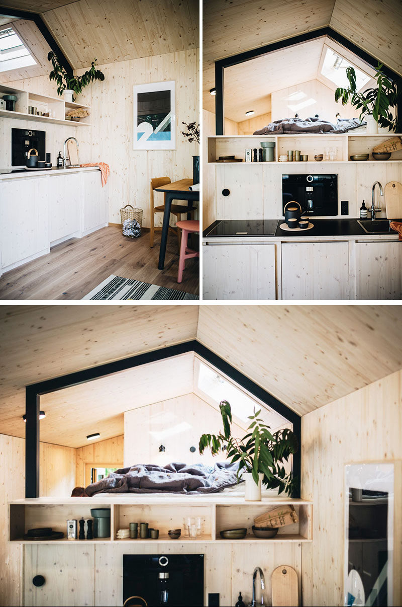 In the small kitchenette of this tiny home, there's a regular size cooktop and a sink, while a fridge and washing machine are hidden within the cabinets below. #TinyHome #UrbanCabin #Kitchenette #Kitchen #LoftBed