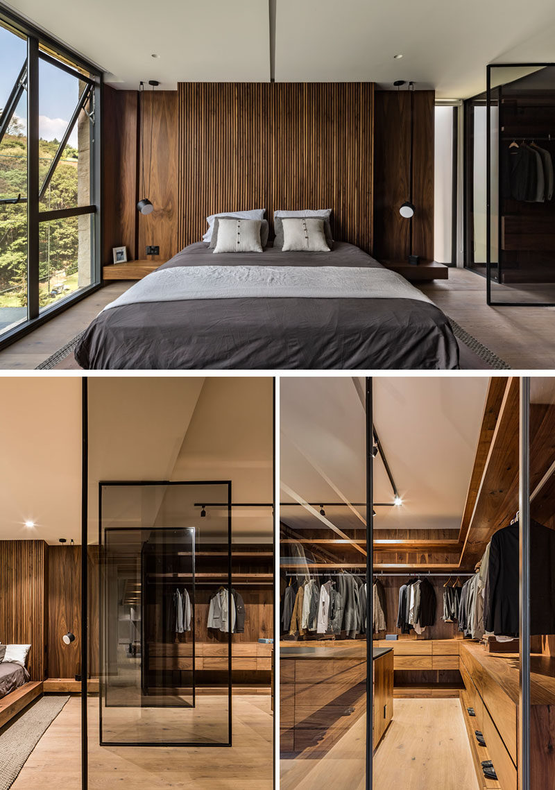 In this modern master bedroom, a rich wood accent wall becomes the backdrop for the bed, while beside the bed, a wall of pivoting glass doors reveal the walk-in closet and dressing room. #MasterBedroom #ModernBedroom #BedroomDesign #Closet #WalkInCloset #DressingRoom