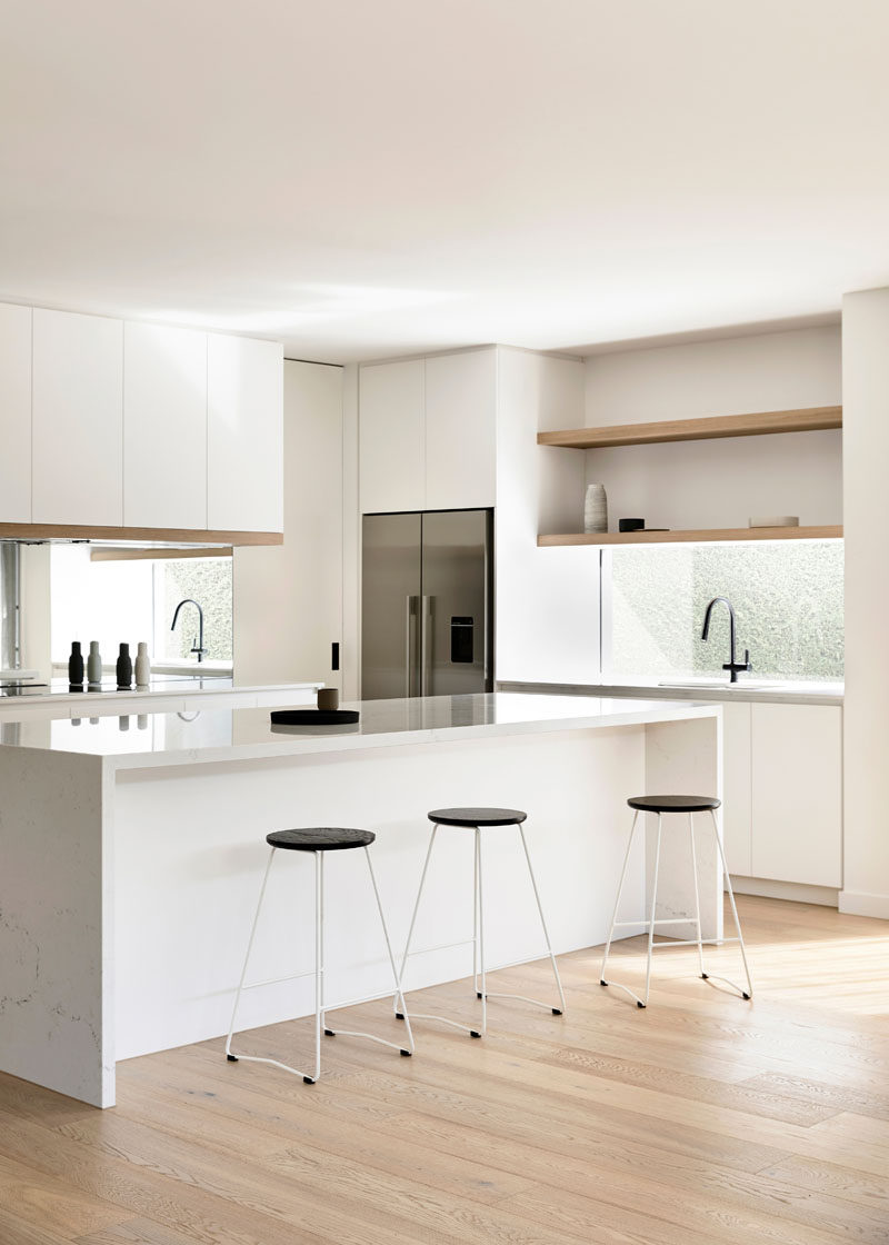 This modern kitchen has bright white cabinets with light wood detailing. A window looking out to the side garden acts as a backsplash, and a mirror below the other cabinets helps to reflect light throughout the space. #WhiteKitchen #WindowBacksplash #MirroredBacksplash