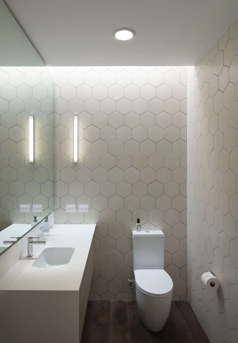 In this modern bathroom, white hexagon tiles cover the walls helping to keep the room bright. #ModernBathroom #WhiteHexagonTiles