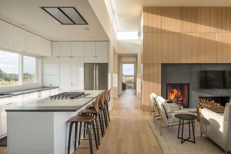 The top floor of this modern house is home to a mostly white kitchen with minimalist cabinets, and an open plan living and dining room. #Fireplace #WhiteKitchen #WoodFloors