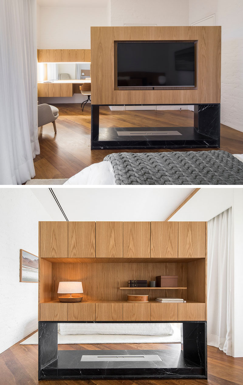 This master bedroom suite has a wood and stone room divider. One side has a cut-out for the television, while the other has cabinets and an open display shelf. A fireplace surrounded by stone is located below the wood top half. #Fireplace #RoomDivider #RoomPartition