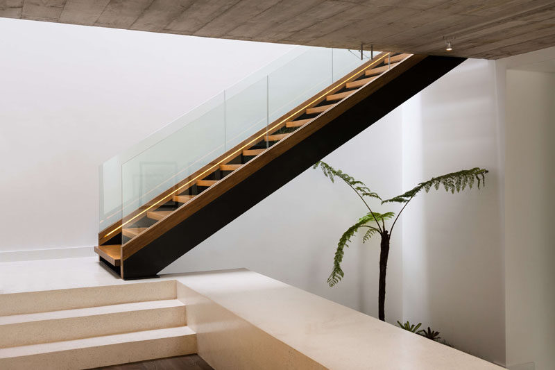 Wood and steel stairs with a glass handrail, located by the front door of this modern house, lead up to the bedrooms. #Stairs #ModernStairs