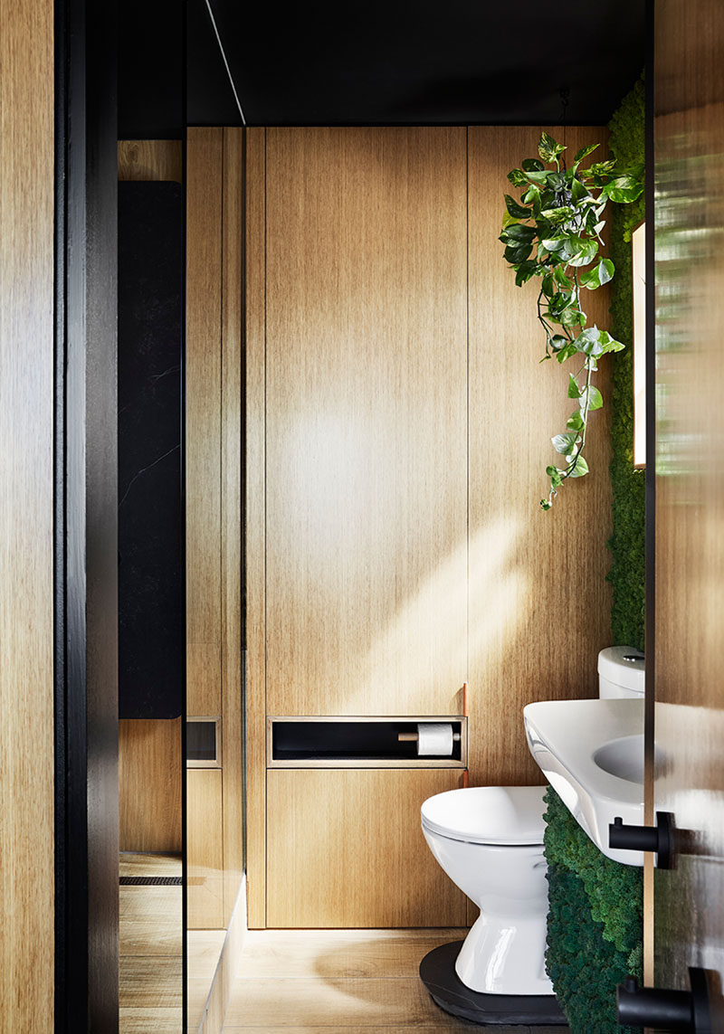 This small and modern bathroom features timber-look porcelain tiles, a green wall, and a fold-down clothes drying rack. #SmallBathroom #BathroomDesign