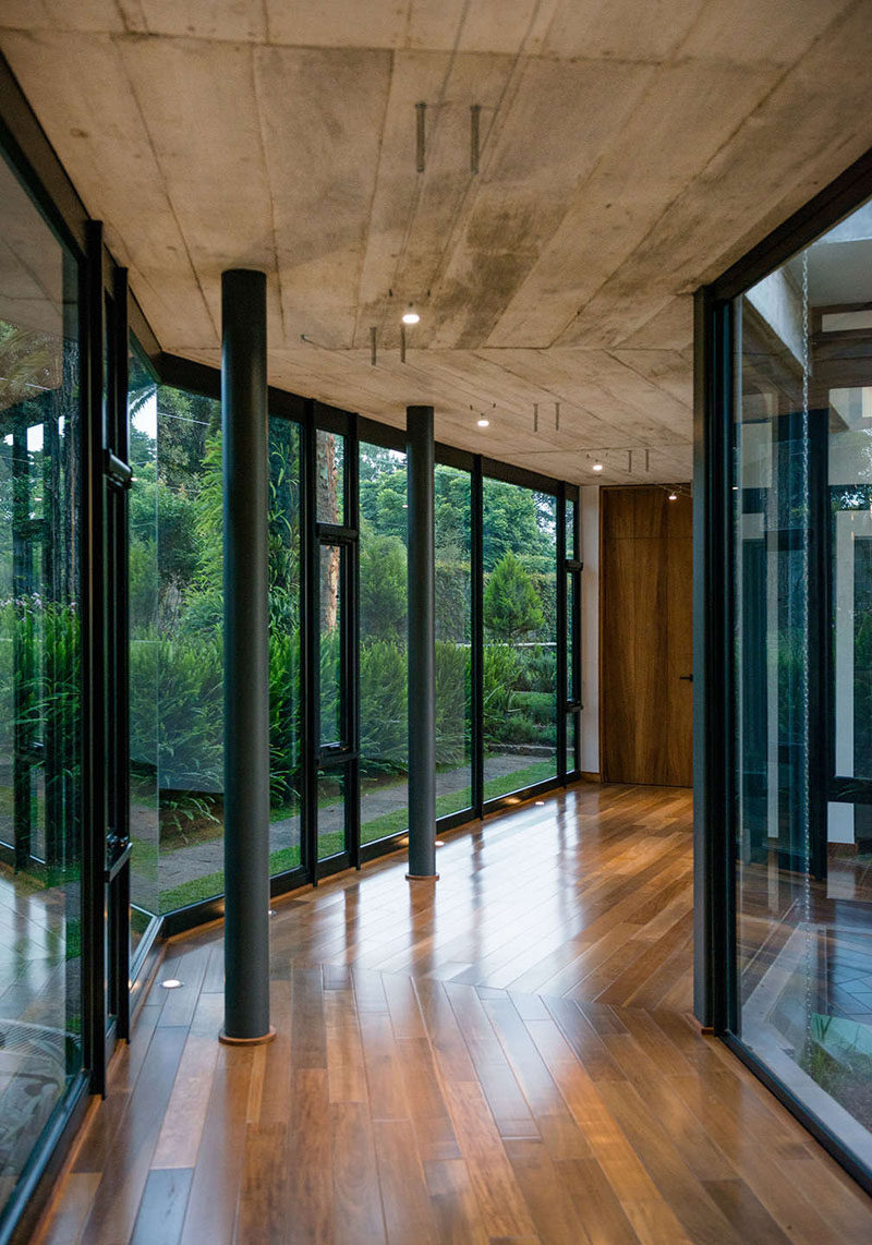 This modern house has hallways with walls of windows, a concrete ceiling, and wood floors. #Hallway #Windows
