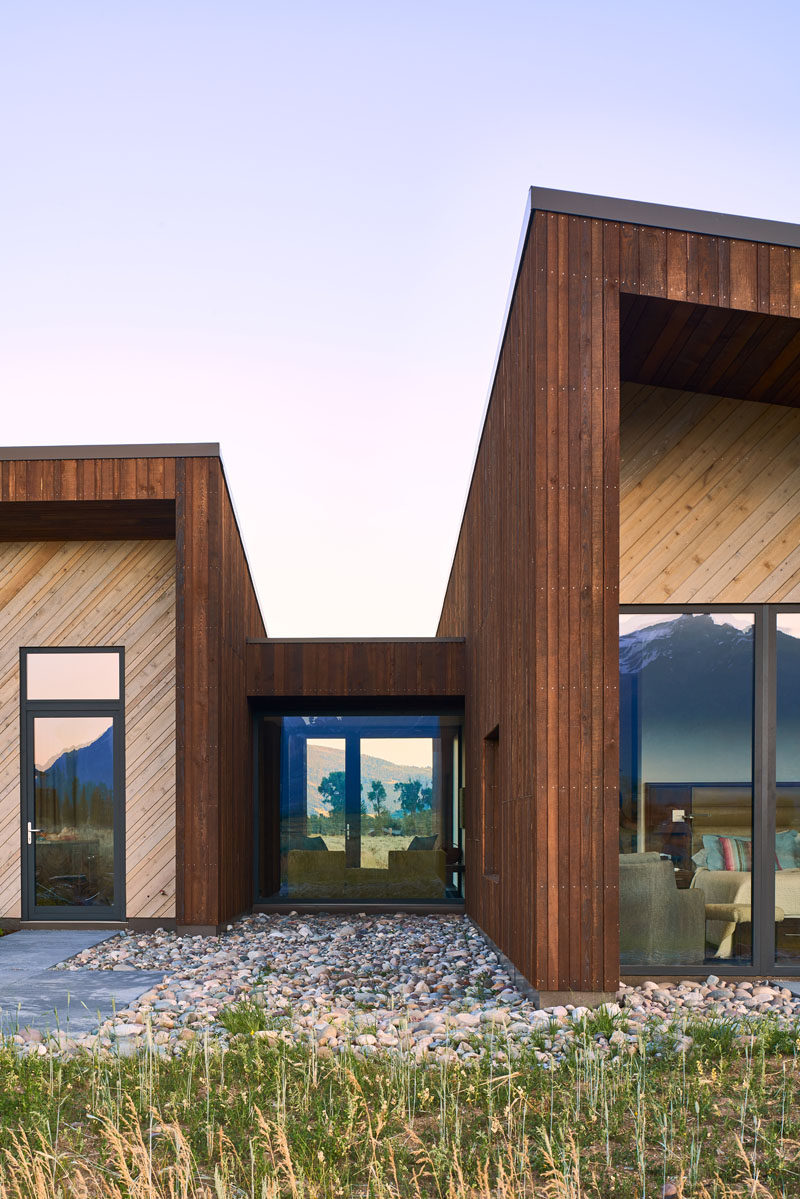 The two-tone exterior of this modern house has been created with the use of rich dark-brown vertical Douglas Fir and lighter horizontal Cedar, allowing the home to meldinto the native woody sage-brush surrounding the home. #WoodHouse #WoodCladding #WoodSiding #ModernHouse #Architecture