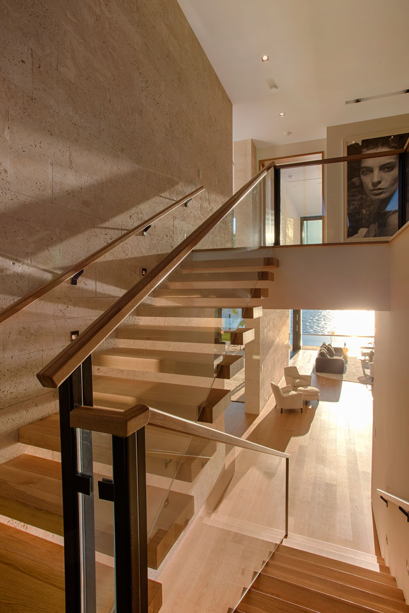 Wood stairs with glass railings connect the various levels of this modern house. #Stairs #ModernStairs