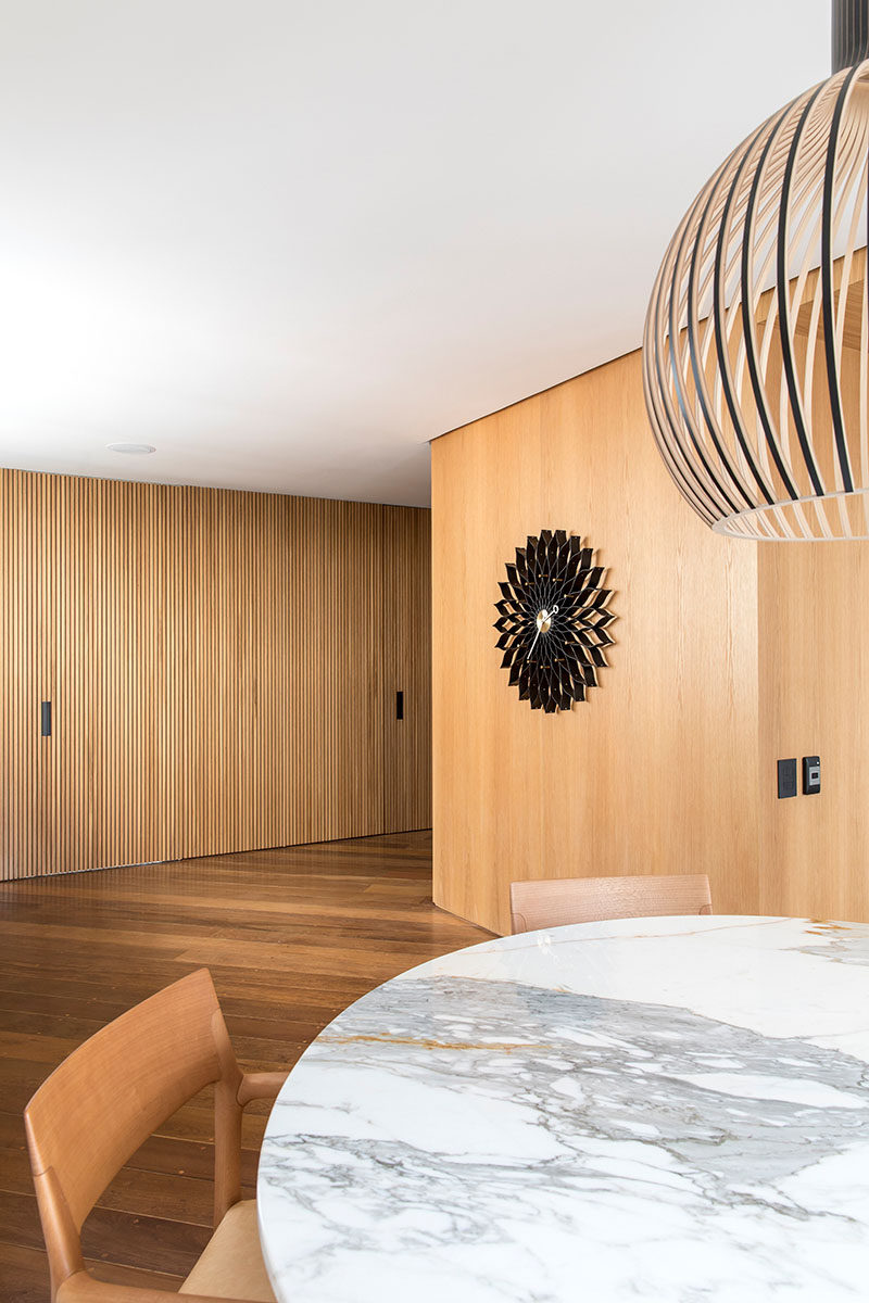The wood slat wall in this room hides doors to a bathroom and storage room. #WoodSlatWall #InteriorDesign