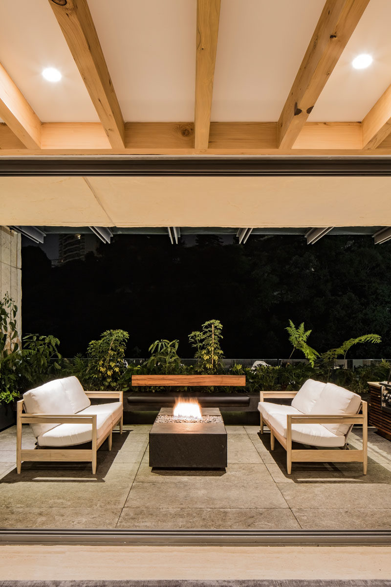 This modern apartment opens to a covered balcony, that has an outdoor sitting area with a tabletop fireplace. #OutdoorSittingArea #Firetable #Balcony