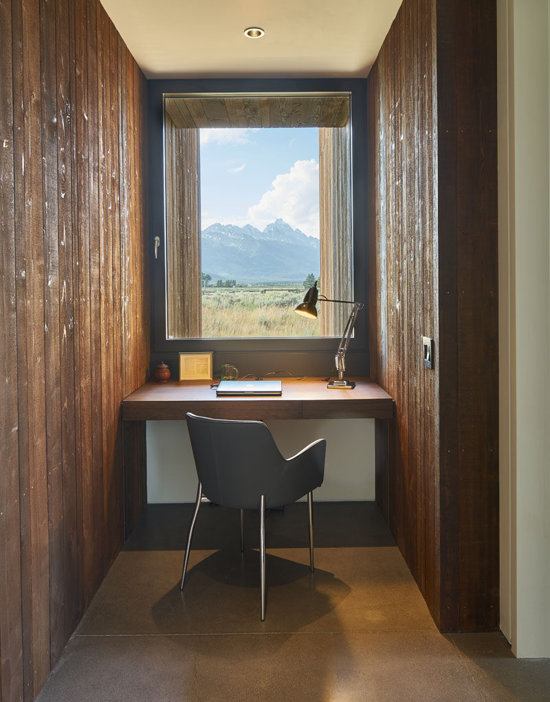 A custom-built office desk is sandwiched between the different pavilions of this modern house, with a window that makes the view beyond almost appear as a piece of framed artwork. #HomeOffice #Desk #Windows #InteriorDesign