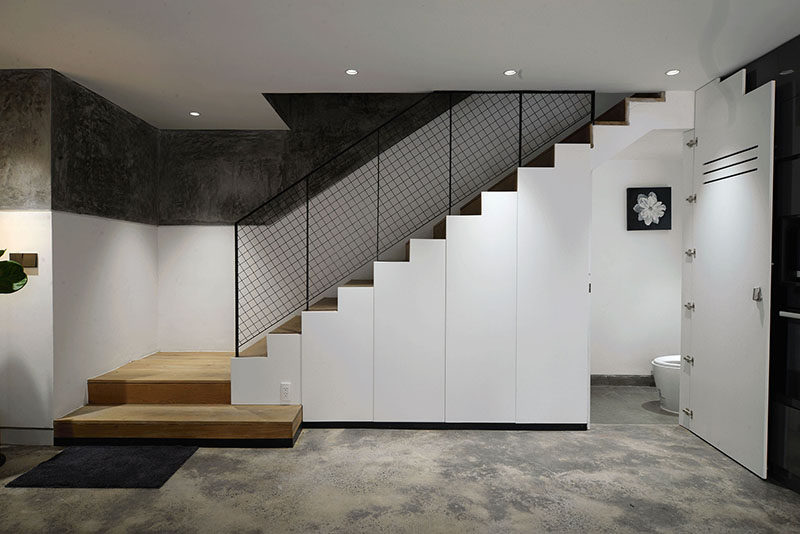 These modern stairs have storage and a small powder room hidden underneath them. #Stairs #StairsWithStorage #PowderRoom
