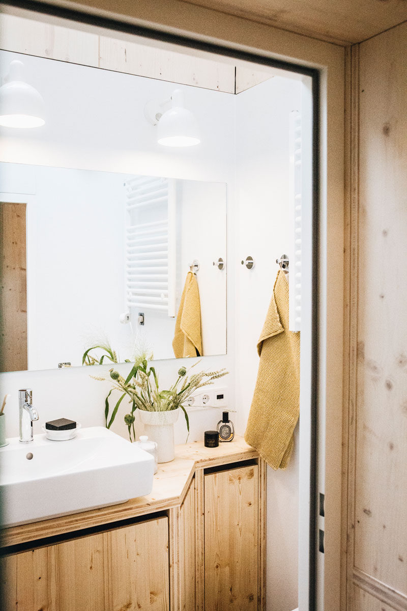 The bathroom in this tiny home has a walk-in rain shower, and natural light from the skylight is reflected in the small room by the mirror, helping to keep it bright. #TinyBathroom #TinyHome