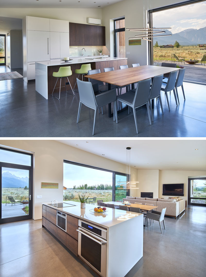 The kitchen cabinet doors and the dining table have been created from a mixture of walnut, mimicking the same hue as the Douglas Fir featured on the exterior of the house. #ModernKitchen #WhiteAndWoodKitchen #WoodDiningTable