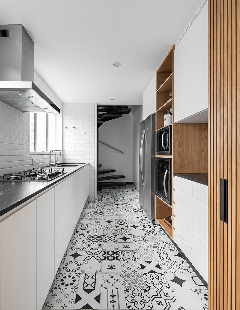 In this modern kitchen, white cabinets have been paired with wood elements, a dark countertop, and patterned floor tiles. #ModernKitchen #PatternedFloorTiles #WhiteKitchen