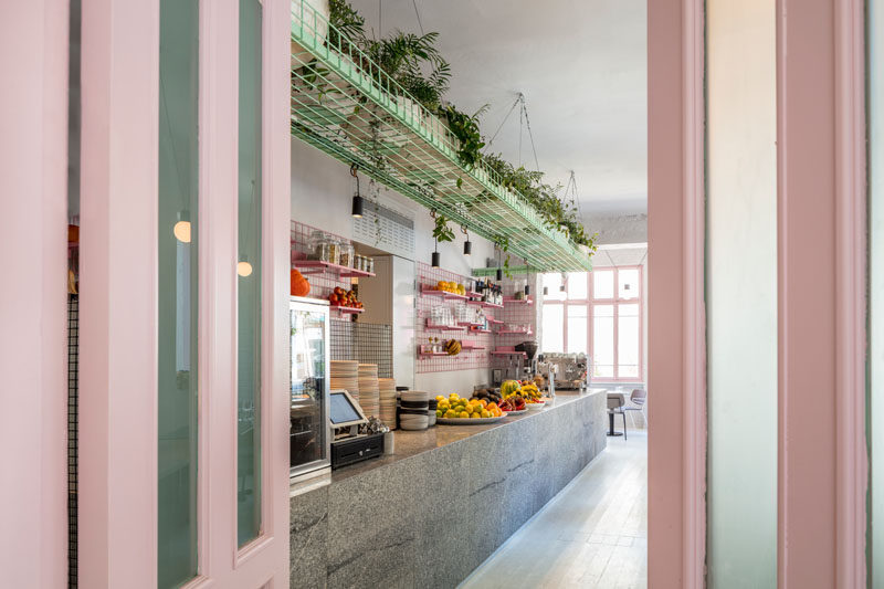 Amit Design Studio has recently completed Bana, an organic food cafe that's located in Tel Aviv, Israel, and has design features like pink metal grid shelving and a large basket filled with plants that hangs from the ceiling. #ModernCafe #CafeDesign #InteriorDesign