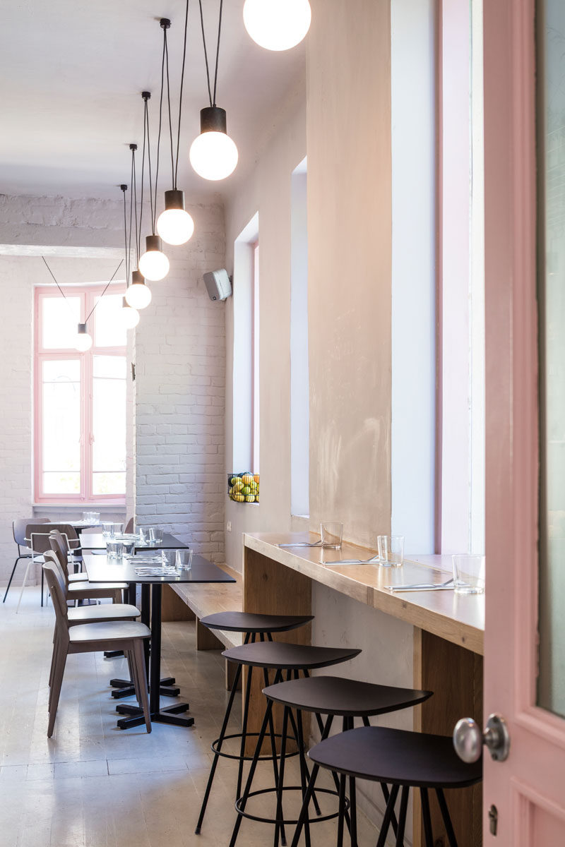A bar height counter is positioned in front of the windows of this modern cafe, while the wood counter continues to become a bench for table seating. #ModernCafeSeating #CafeDesign #InteriorDesign
