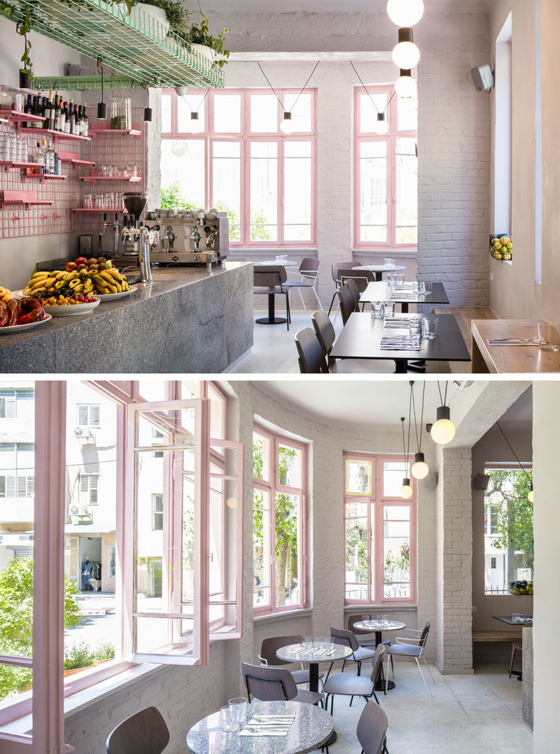 The high ceilings and wood-framed windows of this modern cafe create a feeling of openness, while the original brick walls have been painted in light grey. #CafeDesign #ModernCafe #InteriorDesign