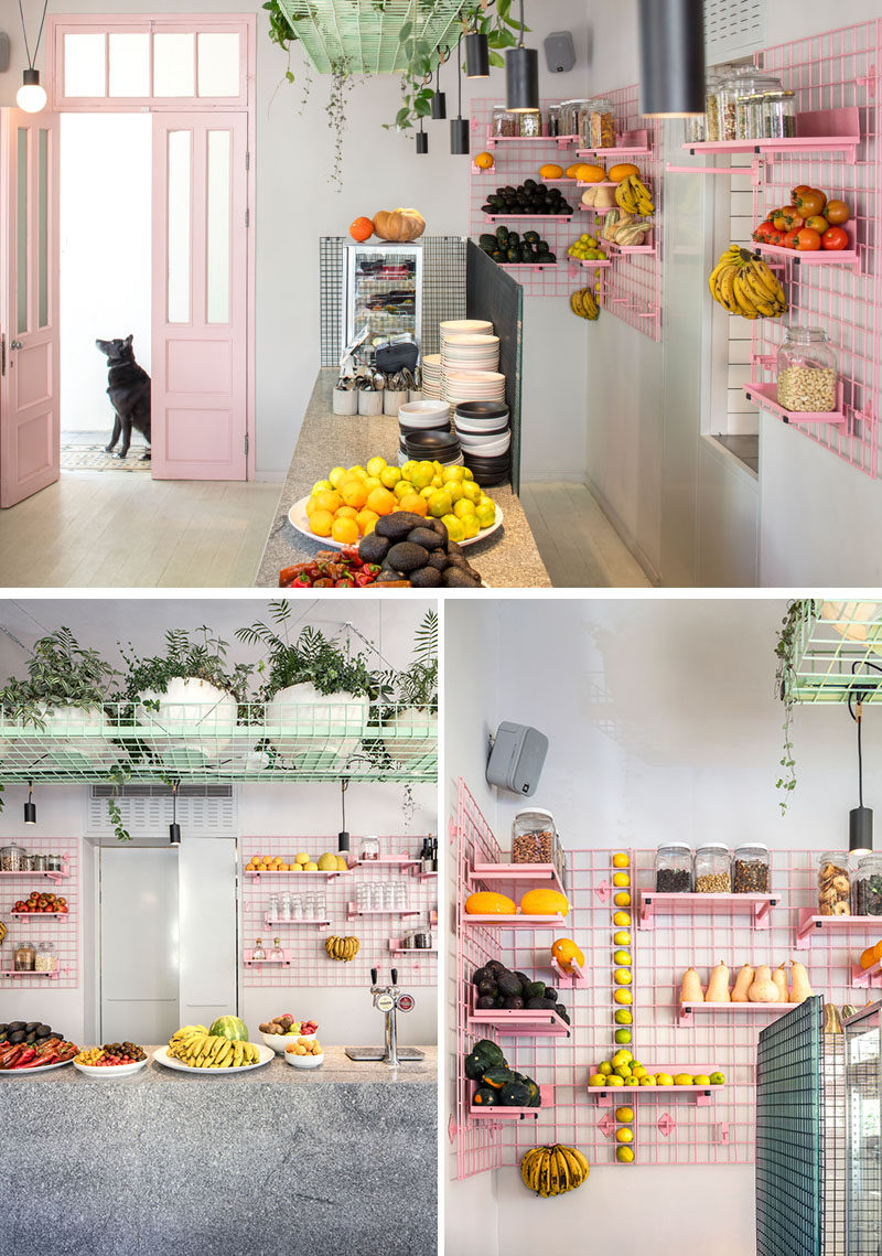 On the wall behind the bar of this modern cafe is a pink metal grid shelving system that allows the shelves to display the fresh fruit and vegetables. Due to the design of the grid unit, the shelves and hooks can be easily moved, depending on the requirements of the day. #Shelving #GridShelving #PinkShelving