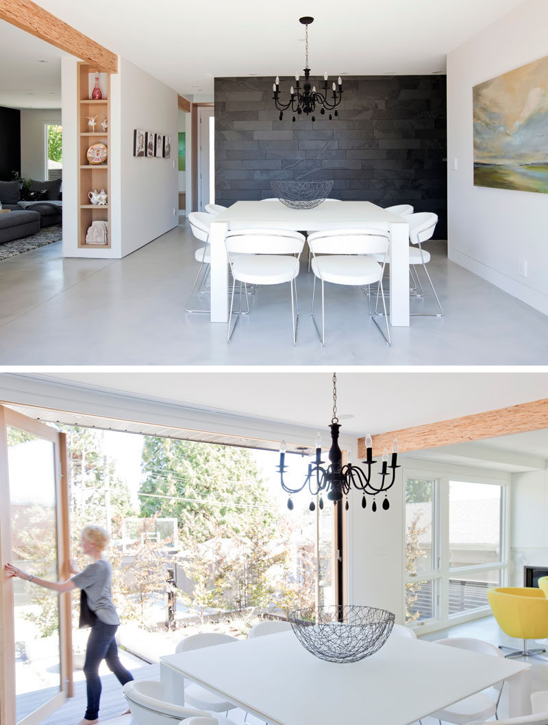 In this dining room, a square white dining table sits below a black chandelier, while an eight foot high scenic door folds away to open the interior to the backyard. #ModernDiningRoom #FoldableDoors
