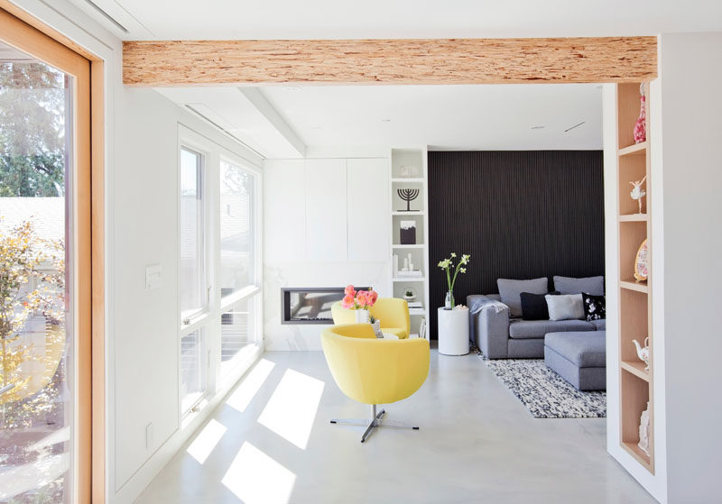 An opening between the living room and the dining room in this modern house, shows off a wood beam, and custom built-in shelving. #WoodShelving #WoodBeam