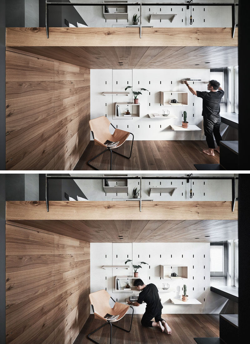 On the lower level of this modern apartment, the space is dedicated to a home office, that features a pegboard wall and allows the shelving to be moved when needed. The wood accent wall hides the door to the bathroom. #ModernApartment #HomeOffice #PegboardWall