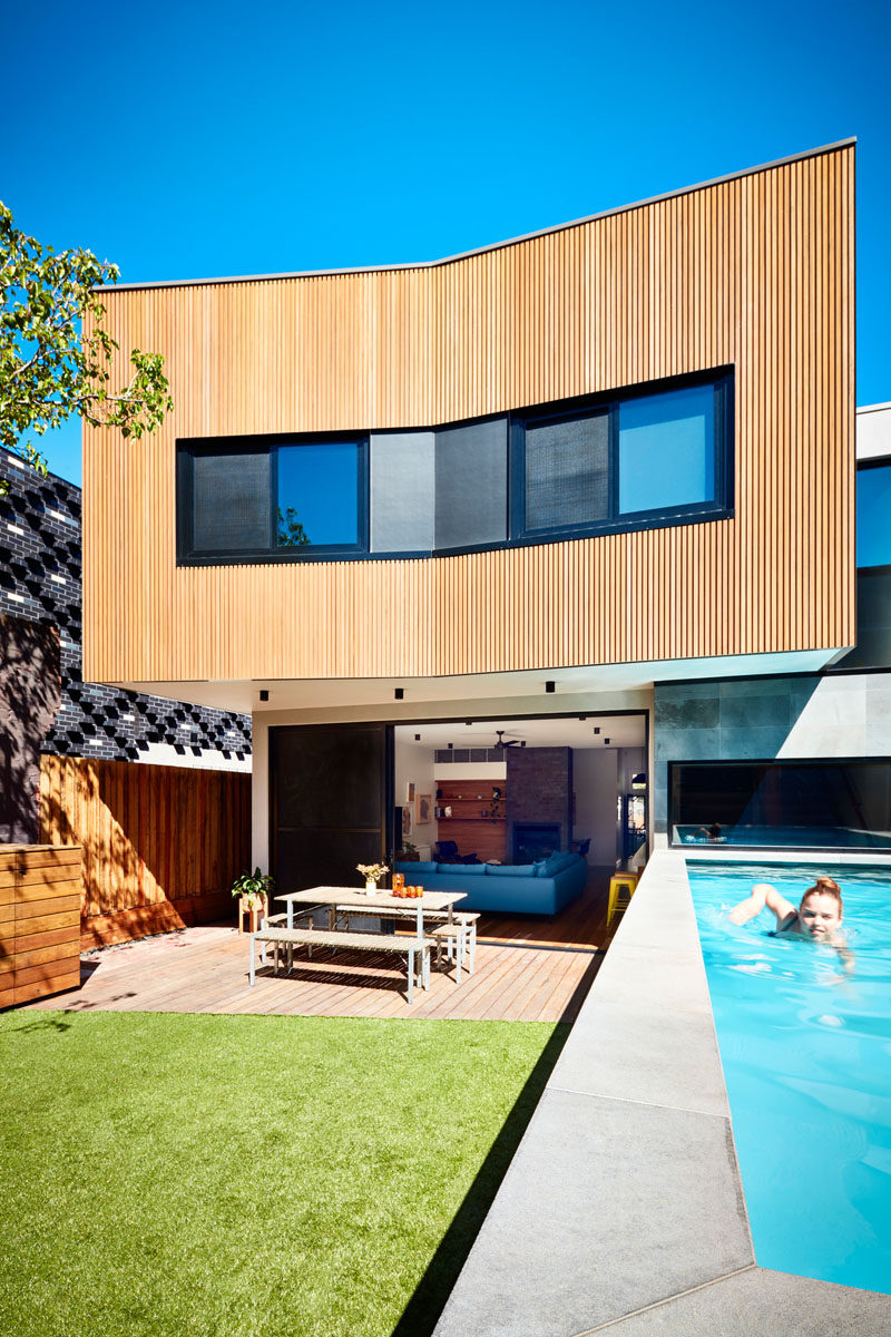 This new and modern wood clad addition opens up to the backyard, where there's a patio, a grassy area, and a swimming pool, which was required to sit above ground due to the local bedrock underneath. #ModernAddition #Wood Architecture #OutdoorSpace #SwimmingPool
