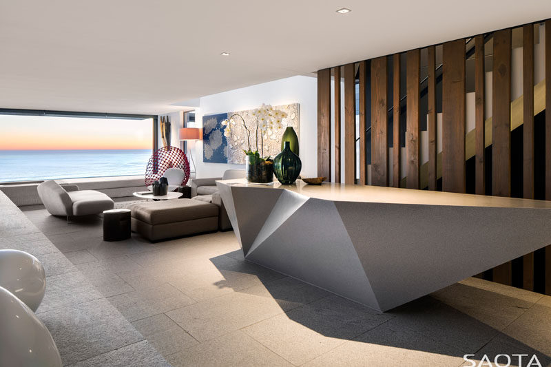 This modern house has a bar lounge, with an angular bar and a seating area that's suspended over the pool. #HomeBar #ModernHomeBar #ModernInteriorDesign