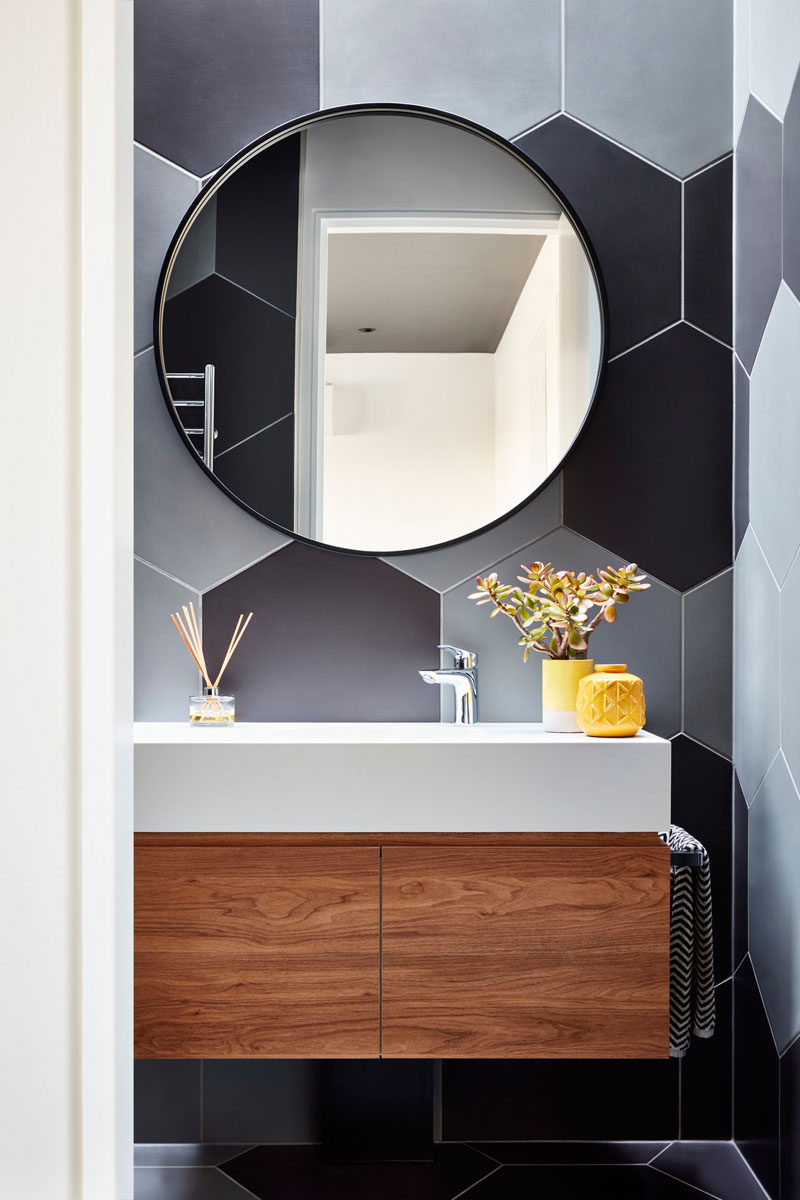 In this modern bathroom, large hexagonal tiles in a variety of grey tones cover the walls and floor. #Bathroom #ModernBathroom #HexagonalTiles