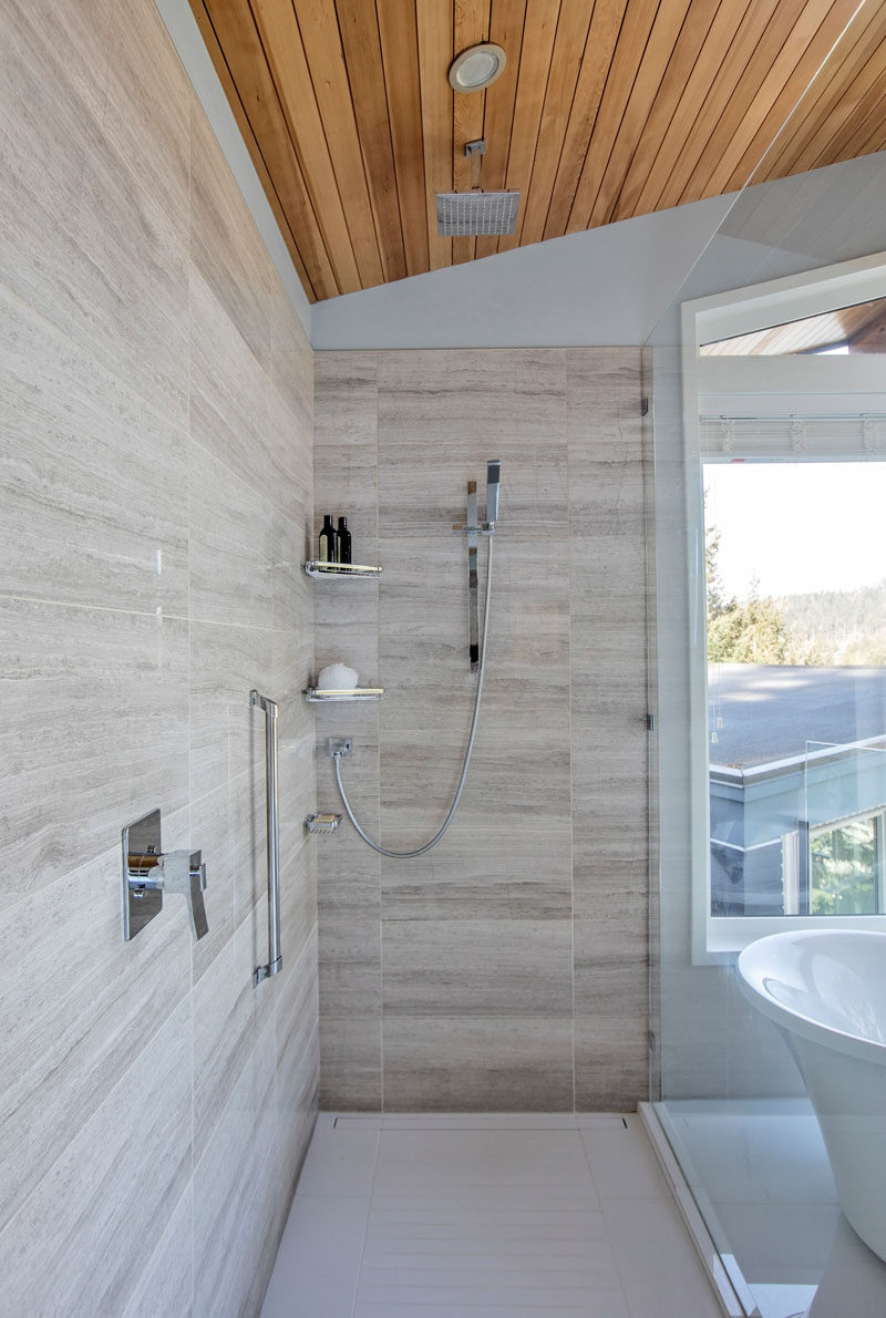 A glass shower screen separates the shower from the bath area in this modern bathroom, and in the shower there's both a rain shower head and a wall mounted one. #Shower #ModernShower