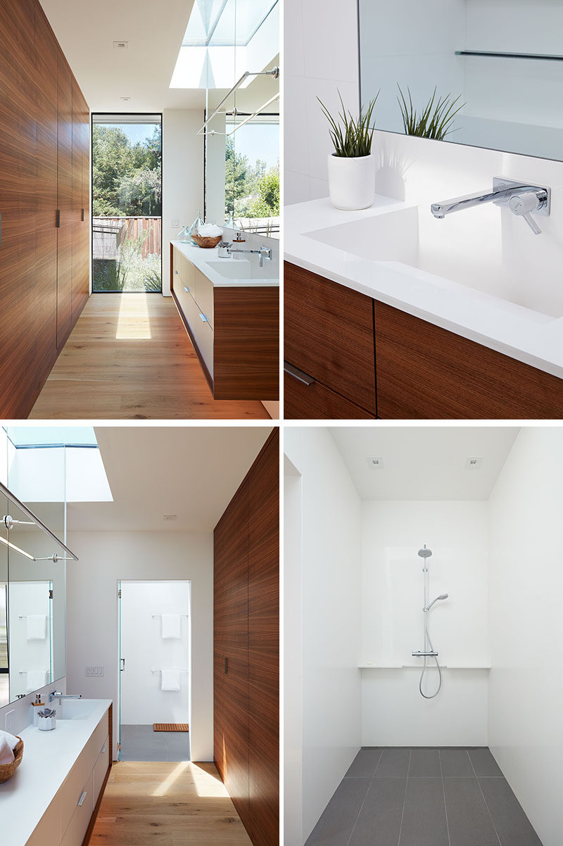 In this modern master bathroom, a wood accent wall hides the door and reflects the wood of the vanity, while the mirror reflects the natural light from the skylight and window. In the shower, grey tiles contrast the white walls and ceiling. #MasterBathroom #BathroomDesign