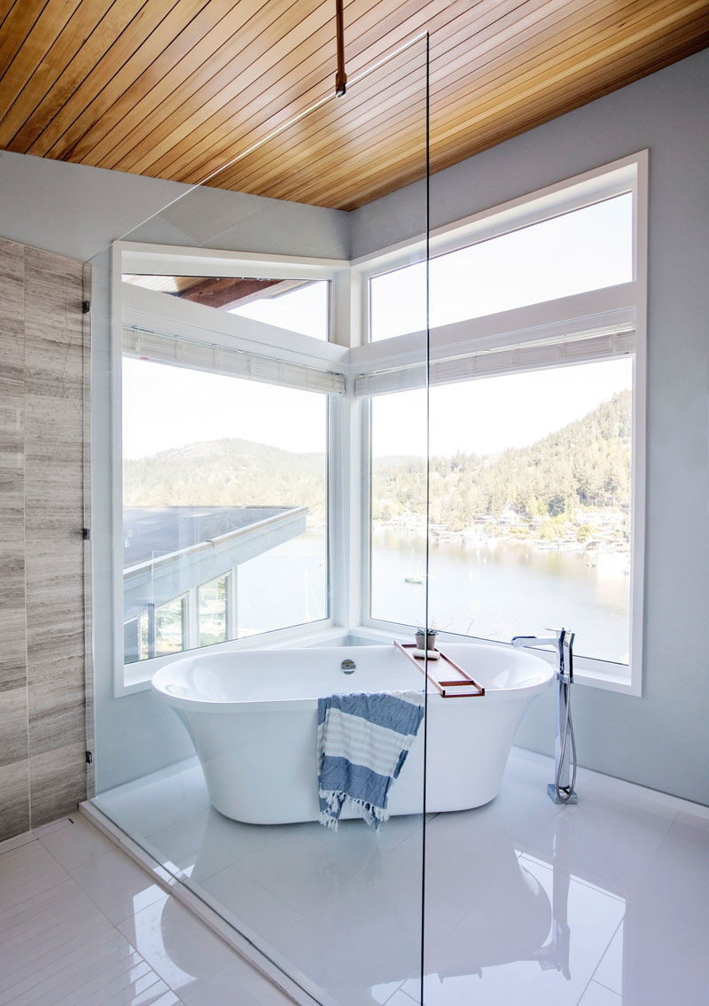 In this modern master bathroom, a freestanding bathtub is positioned below the windows to take advantage of the views. #BathroomDesign #Windows