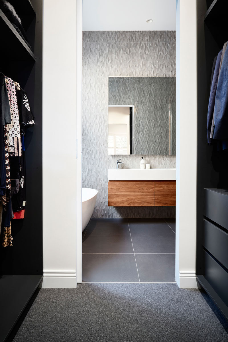 In this master bedroom, a walk-in closet is located off the bathroom, where the wood vanity complements the wood used in the bedroom. #ModernBathroom #GreyBathroom #WalkInCloset