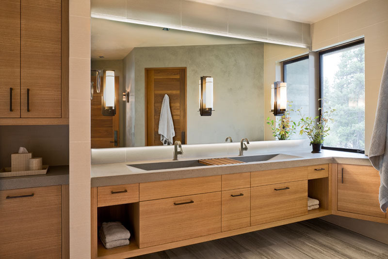 In this modern guest bathroom, a floating wood vanity is topped with a custom concrete countertop, while a large backlit mirror reflects light throughout the room. #ModernBathroom #ConcreteCounter #WoodVanity