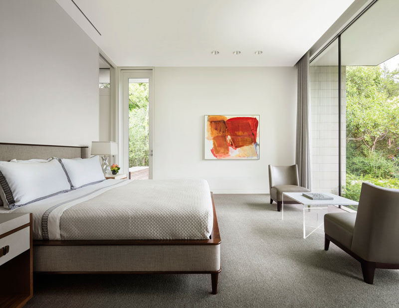 This modern master bedroom has large windows that flood the interior with natural light, and provide a view of the front garden. #MasterBedroom #Windows