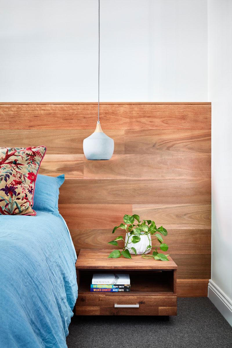 This modern master bedroom has a wood headboard, floating wood bedside tables, and modern pendant lights. #ModernBedroom #BedroomDesign
