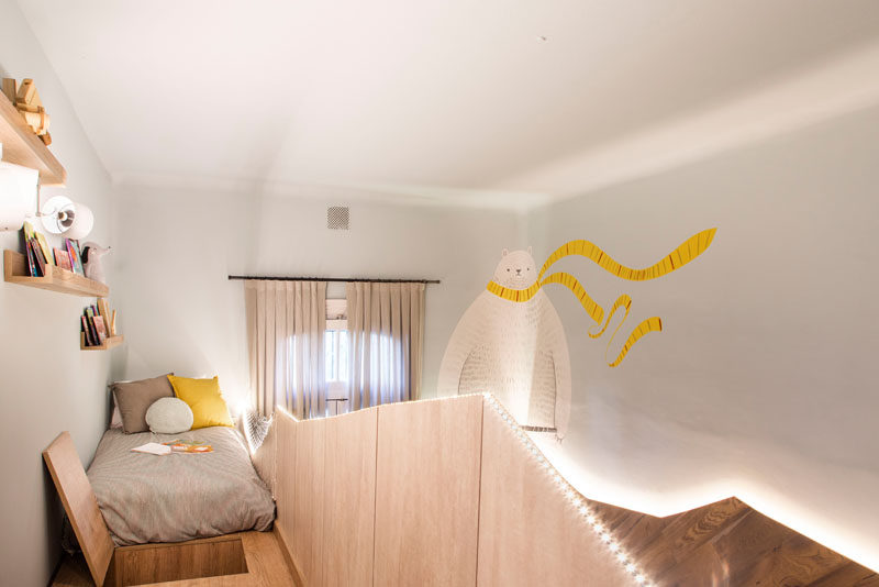 This modern kids bedroom has a bunk bed with a view of the large painted polar bear mural on the opposite wall. #BunkBed #KidsBedroom #Shelving #WallMural
