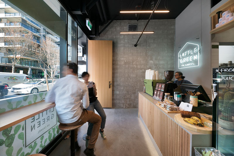 In this small and modern cafe, bar seating along the window provides a place for people to wait for their food while viewing the street. #CafeDesign #InteriorDesign