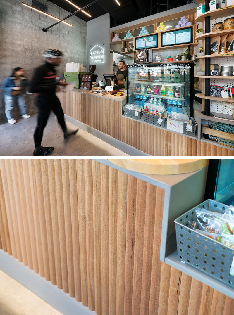 The service counter has a textured wood facade that complements the other wood elements in this modern cafe, and the counter drops down to a different height to display product and create visual interest. #CafeDesign #InteriorDesign #ServiceCounter