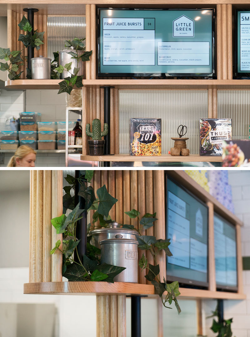 Custom designed wood shelving provides a place for displaying plants, products, and menu boards, in this small and modern cafe. #Shelving #CafeDesign #WoodShelving