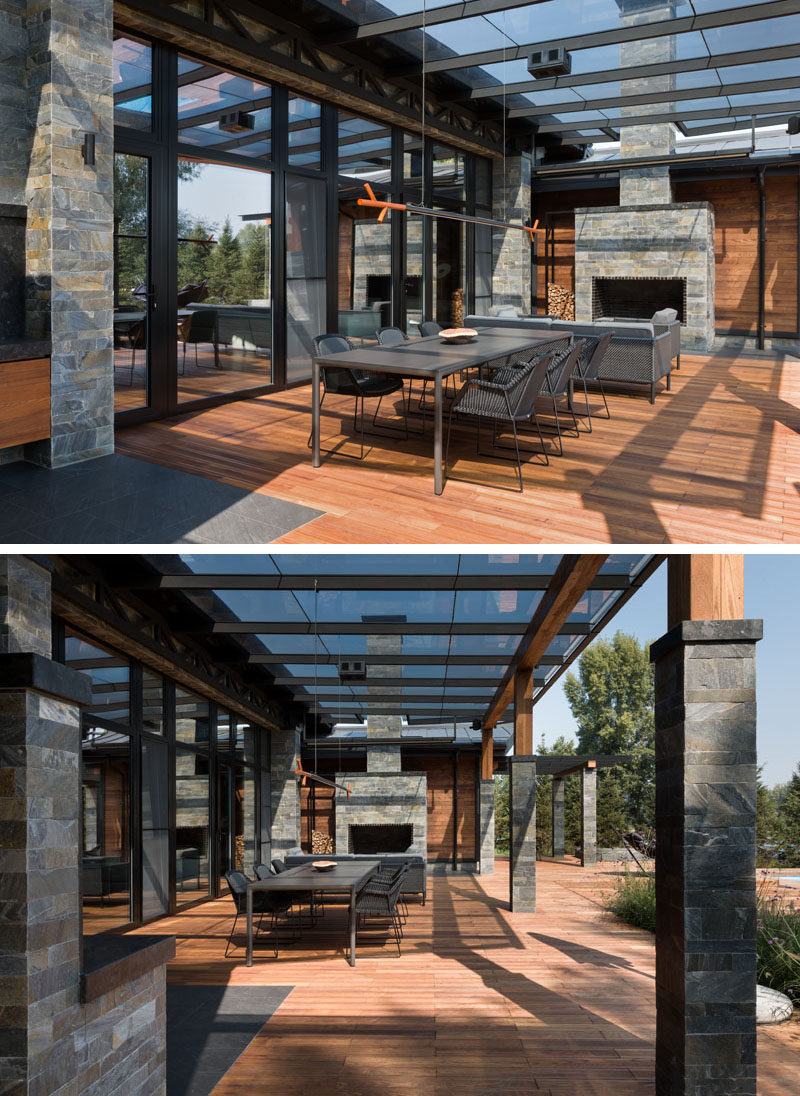 This modern house has a covered patio with an outdoor dining area, a lounge and a stone-clad fireplace. #Patio #CoveredPatio #OutdoorSpace #Fireplace