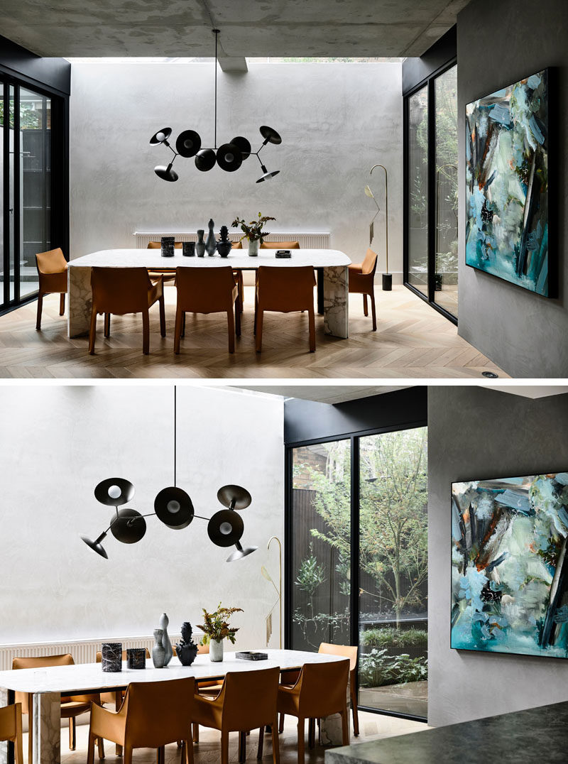 A skylight highlights this modern dining room, while a sculptural chandelier anchors the dining table in the open room. #DiningRoom #ModernDiningRoom