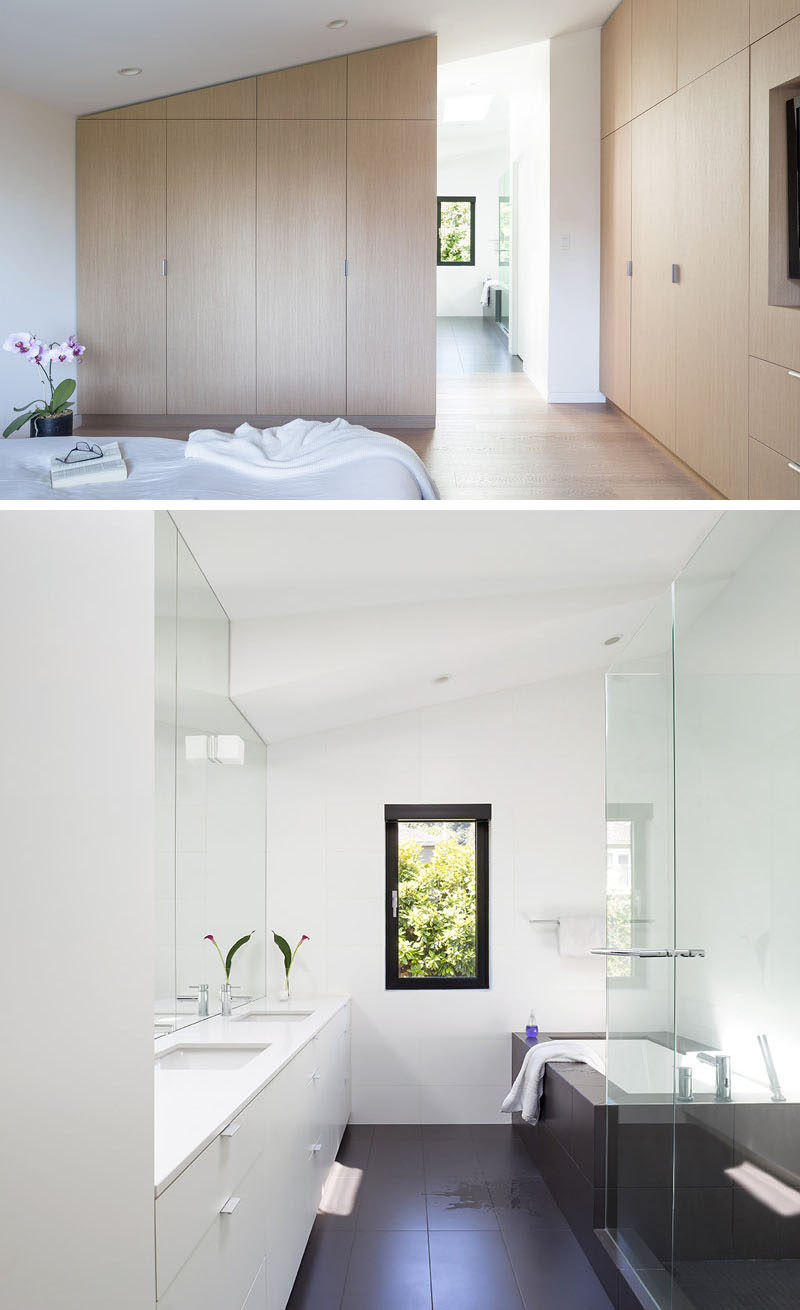 In this modern master suite, minimalist light wood cabinets line the walls, while natural light from the bathroom with a built-in bathtub flows through to the bedroom. #ModernMasterSuite #ModernBathroom #ModernBedroomClosets #BuiltInBathtub
