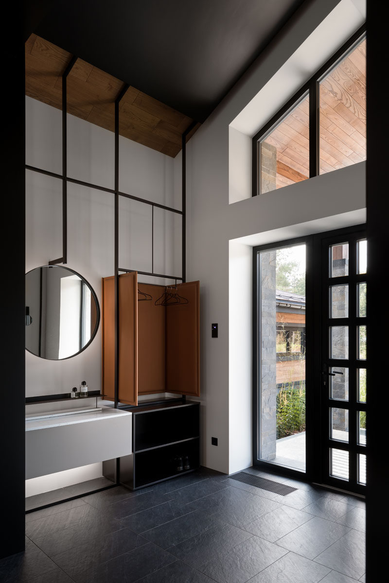 Stepping inside this modern house, the high ceilings throughout the home are immediately apparent. A custom designed multi-purpose furniture piece in the entryway provides a place to hang jackets and store shoes. #Entryway #ModernInteriorDesign #HighCeilings