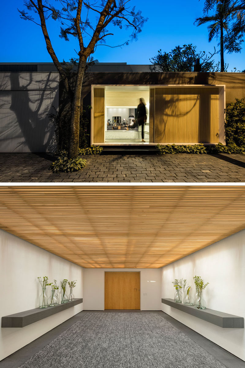 A wood front door with entrance hall welcomes people to this modern house and guides them inside. #WoodFrontDoor #EntranceHallway