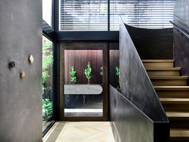 A glass front door welcomes visitors to this modern house, and once inside the double height ceilings and windows allow the entryway to be bright and open. #ModernFrontDoor #GlassFrontDoor #SteelStairs