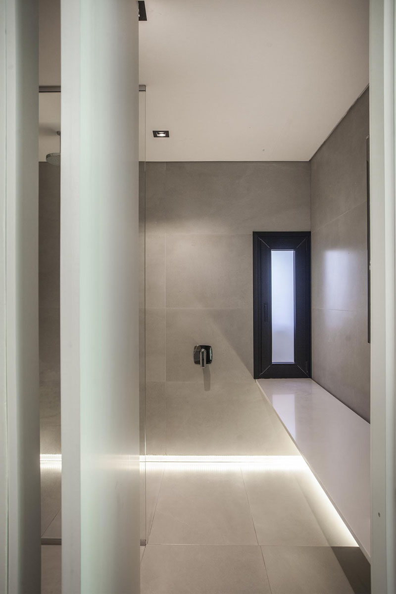 In this modern grey and white bathroom, lighting has been installed where the walls meet the floor, creating a unique light element that draws attention. #ModernBathroom #BathroomDesign #InteriorDesign #Lighting